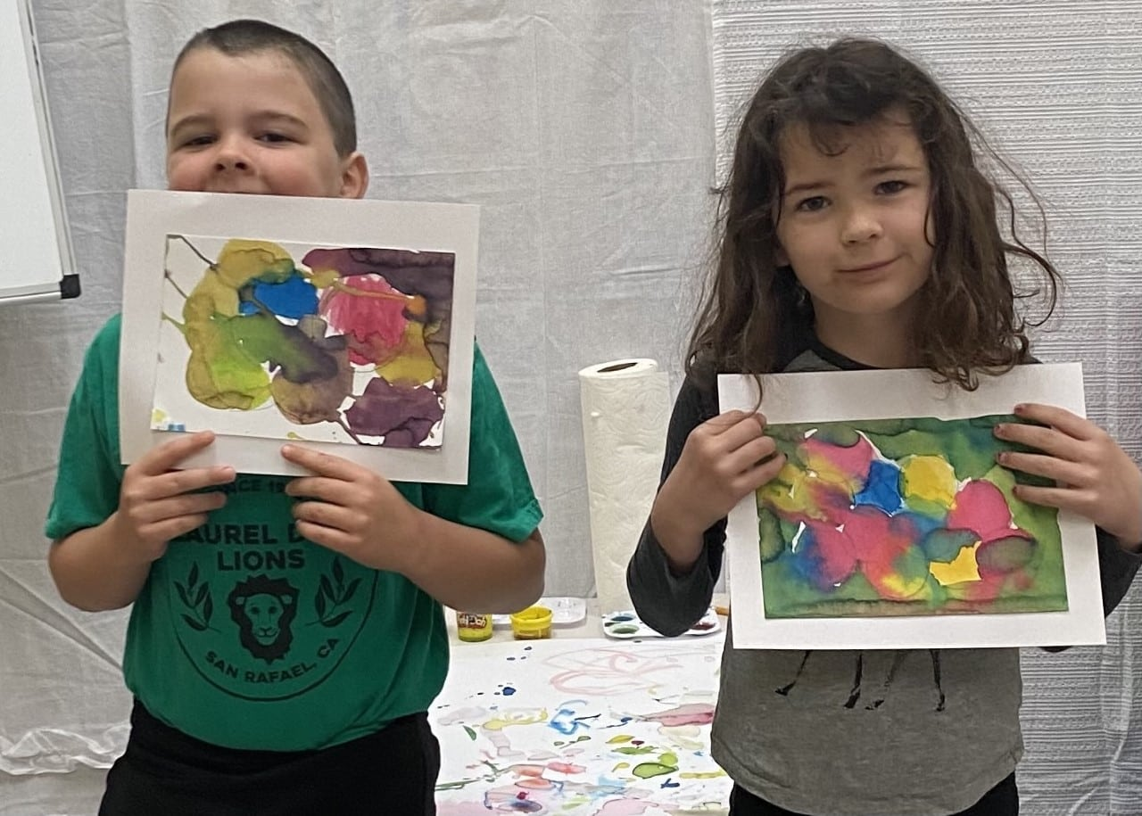 Laurel Dell Elementary siblings show off their art from the Youth in Arts COR program funded by HeadsUp with support from SchoolsRule